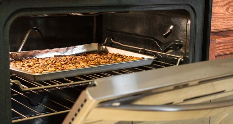 Pumpkin Seeds Roasting in Oven on Baking Sheet