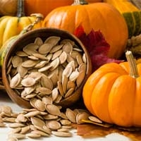 Roasted Pumpkin Seeds in Bowl and Small Pumpkins