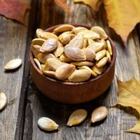 Salty and Sweet Roasted Pumpkin Seeds in Bowl with Fall Leaves