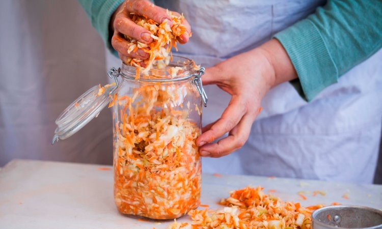 filling jar with cabbage for fermenting