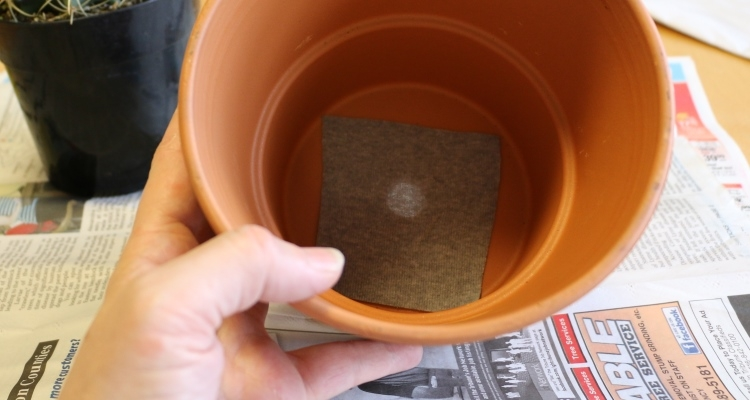 cover the drainage hole of a pot with a thin piece of scrap fabric