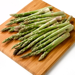 Pile of Asparagus on wooden cutting board